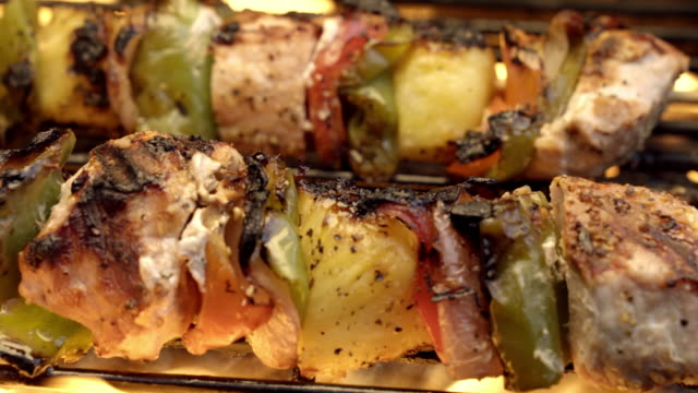 pork chicken shish kebabs on a fiery grill with peppers and pineapple - spiedino video stock e b–roll