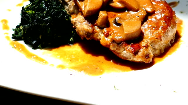 Pork chop meat steak with vegetable in white plate video