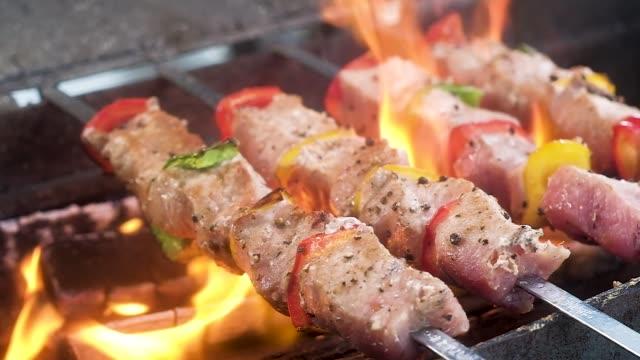 fläsk läcker shish kabobs genomborrade med spett. kött med röd, gul, grön peppar, stänkade kryddor. stekt på öppen eld på en kolgrill i tungor av ljus varm flamma. från mat går ånga. - grillspett bildbanksvideor och videomaterial från bakom kulisserna