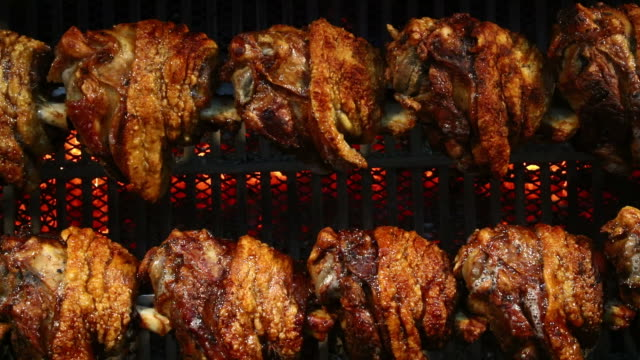 Pork knuckles slowly cooked at rotation grill video