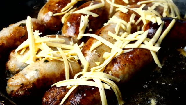 Pork or chicken sausages are fried in frying pan in boiling vegetable or olive oil and sprinkled with grated cheese. Preparations homemade sausages. Step by step. Pork or chicken sausages are fried in frying pan in boiling vegetable or olive oil and sprinkled with grated cheese. Home fast food. Close up. roast dinner stock videos & royalty-free footage