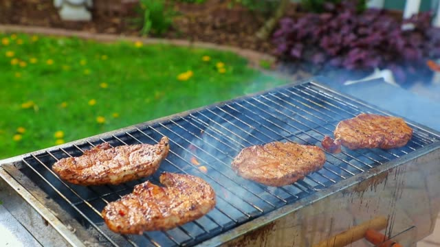 Pork steaks are turned on the grill in the garden with grill tongs Pork steaks are turned on the grill in the garden with grill tongs. pork stock videos & royalty-free footage