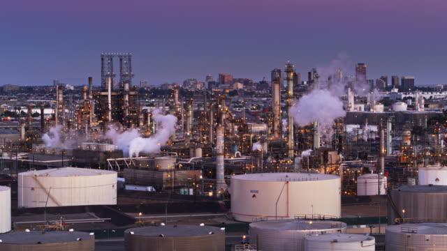 stockvideo's en b-roll-footage met poort olieraffinaderij verlicht bij zonsondergang - drone shot - chemische fabriek
