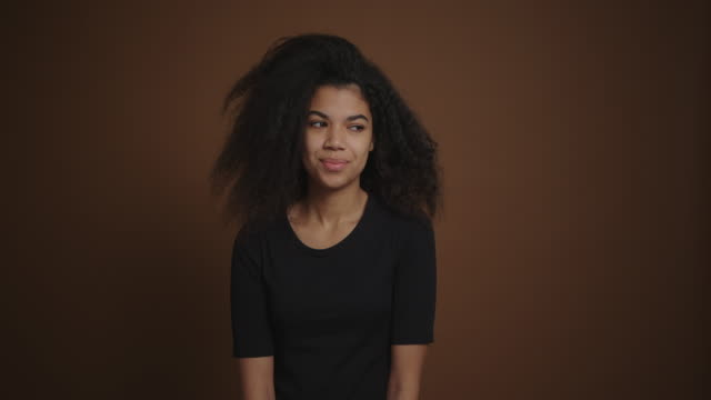 portait of african american girl looking coquettishly at camera brown background - occhiata laterale video stock e b–roll
