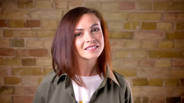 Portait of young attractive brown-headed woman watching smilingly into camera on bricken wall background. Portait of young attractive brown-headed woman watching smilingly into camera on bricken wall background sideways glance stock videos & royalty-free footage