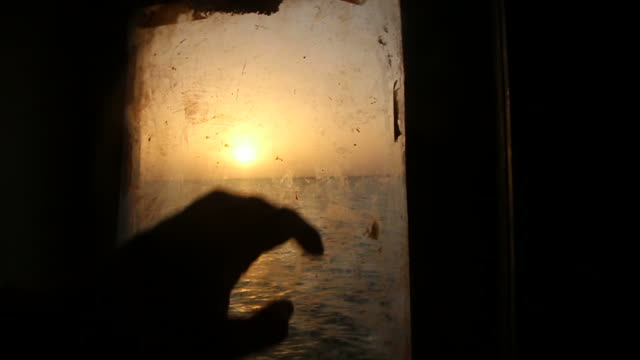 Porthole revealing sunset over water video