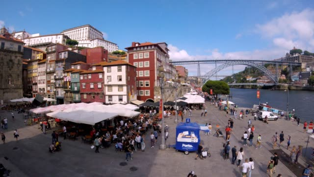 Porto Portugal - July 30 2018: Crowded Porto Ribeira square view in walking loop-able time-lapse with Dom Luís I Bridge and river Douro during beautiful sunny day