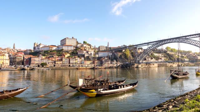 vídeos de stock, filmes e b-roll de lapso de tempo 4k de porto portugal, skyline da cidade timelapse em porto ribeira e rio de douro com o barco de vinho de rabelo - porto distrito