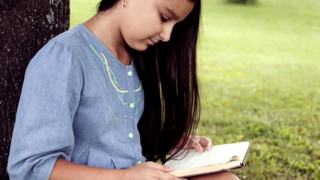 Portrait. A beautiful little girl with long hair reads a book sitting under a tree and dreams about something pleasant smiling video