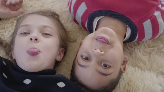 Portrait African American boy and blond caucasian girl lying on the floor.