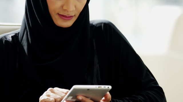 portrait arabic businesswoman using wireless tablet city office - cartello economico video stock e b–roll