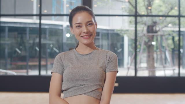ヨガのクラスで幸せな楽しみを感じる肖像画アジアの日本人女性。韓国の女の子は、フィットネススタジオで健康的なライフスタイルを行使しながら、カメラを探して歯の笑顔をリラックス� - スタジオ 日本人点の映像素材/bロール