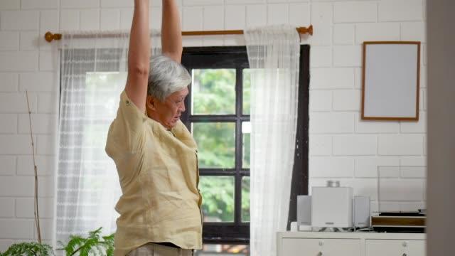 portrait asian senior man exercise in living room at home. - rozciągać filmów i materiałów b-roll