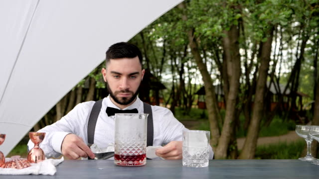 portrait bartender adds ice to glass of liquor on bar counter, barman put ice into glass with alcohol and holding napkin video