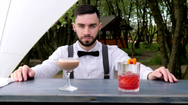 portrait bartender behind bar, barmen submit alcohol, barkeeper close-up, colored chilled drinks on bar counter, beautifully decorated video