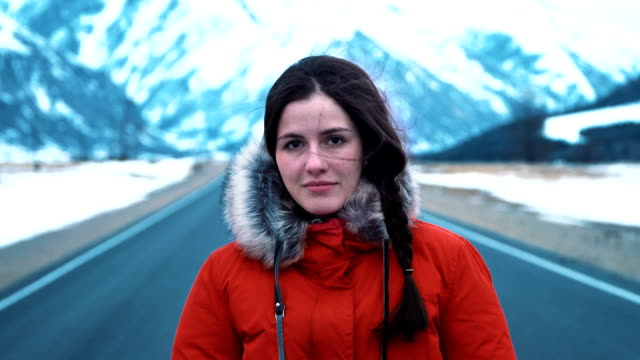 Portrait: beautiful girl stands on road or highway in winter against the backdrop of the mountains video