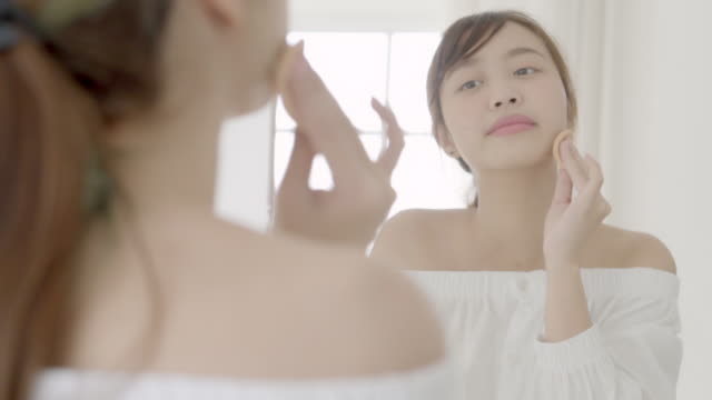 Portrait beautiful young asian woman applying powder puff at cheek makeup of cosmetic looking mirror, lifestyle of beauty  girl with skin face smile in the bedroom, health and wellness concept.