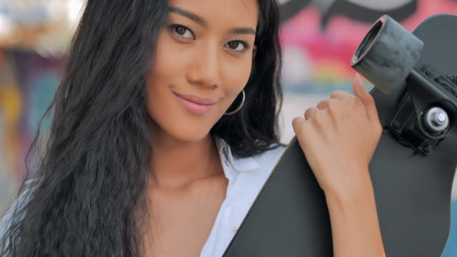 Portrait black teenager girl holding a skateboard looking at camera.Lifestyles, Extreme Sports, People, Leadership, Portrait ,Confidence concept.South East and East Asia: Young Adults Enjoying Extreme Sports - vídeo