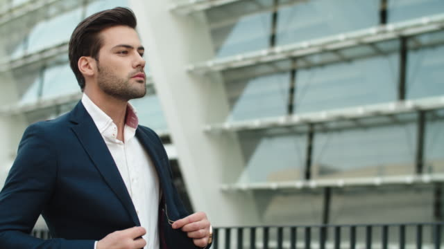 Portrait businessman walking outdoors. Man looking away outdoors at city