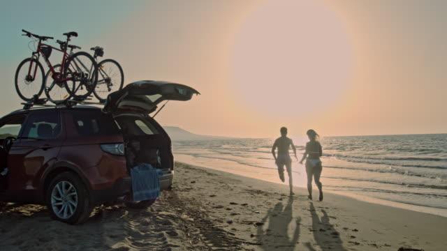 vidéos et rushes de ms portrait couples insouciants agitant et courant sur la plage ensoleillée de mer, pouilles, italie - homme faire coucou voiture