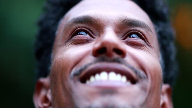 portre yakın çekim yüz adam gökyüzüne umut ve inanç duygu bakarak - hıristiyanlık stok videoları ve detay görüntü çekimi