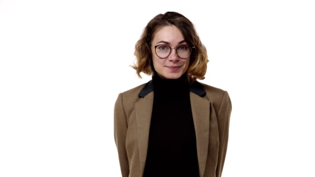 Portrait closeup of adorable european woman wearing brown jaket and stylish glasses, curly short hairstyle posing on camera with lovely smile and wink once, isolated over white background
