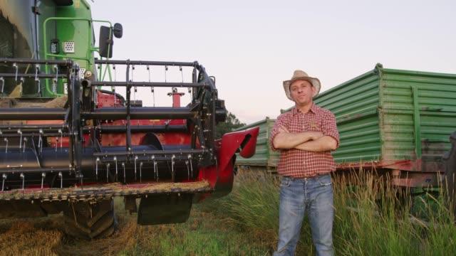 Portrait confident farmer standing at combine harvester,slow motion