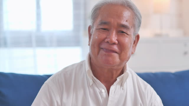 成功したライフスタイルを楽しむ幸せな感情で自宅で一人でポーズをとっているカメラでコミュニケーションしながら微笑むアジアの高齢の祖父の肖像画。ビデオ会議技術に関する社会的な� - 人里離れた点の映像素材/bロール