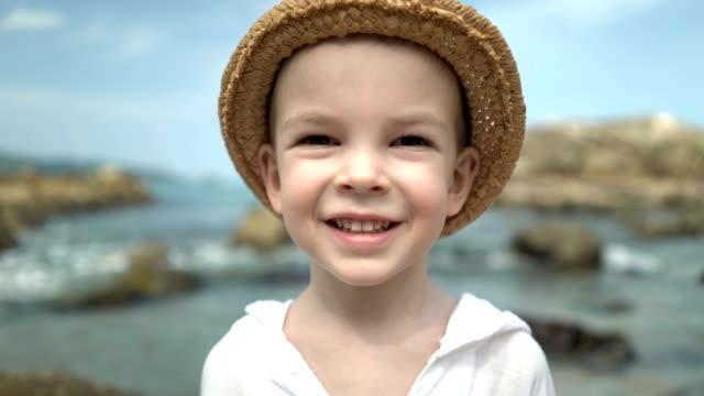 ビーチの麦わら帽子の肖像かわいい男の子。UHD ビデオ ビデオ