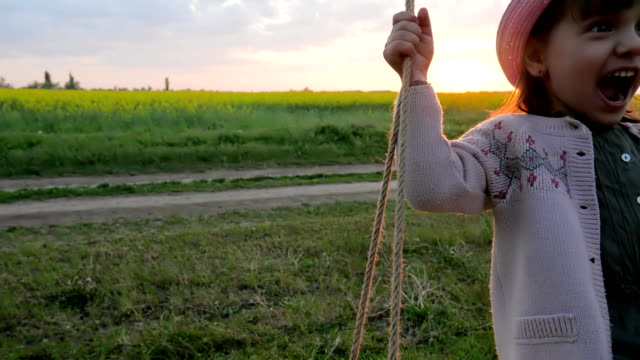 niedliche mädchen porträt schüttelt auf hängen vom baum swing, kinder auf der schaukel, weibliche kind wiegen, glückliches kleines kind viel spaß sway - kind schaukel stock-videos und b-roll-filmmaterial