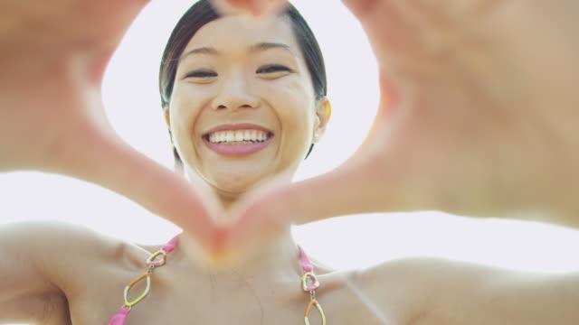 vidéos et rushes de femme ethnique portrait mains tournage selfie de forme de coeur - évasion du réel