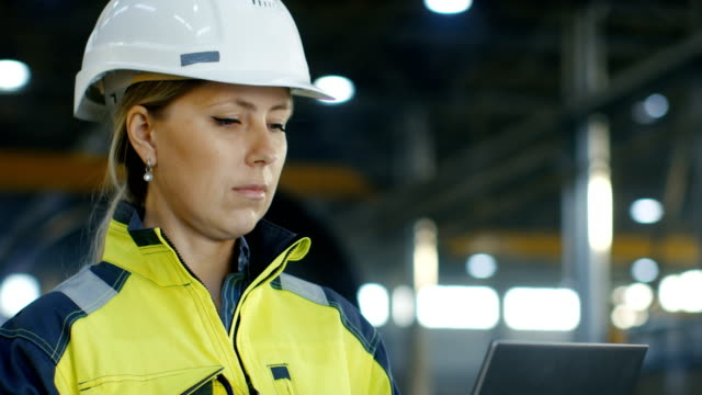 Portrait Female Industrial Engineer in the Hard Hat Uses Laptop Computer while Standing in the Heavy Industry Manufacturing Factory. In the Background Various Metalwork Project Parts Lying Portrait Female Industrial Engineer in the Hard Hat Uses Laptop Computer while Standing in the Heavy Industry Manufacturing Factory. In the Background Various Metalwork Project Parts Lying  Shot on RED EPIC-W 8K Helium Cinema Camera. quality control stock videos & royalty-free footage