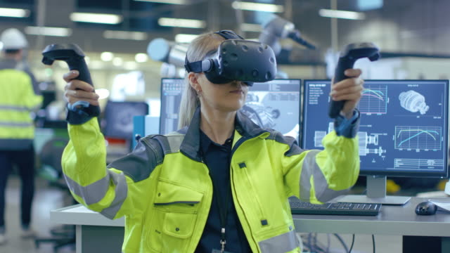 portrait female mechanical engineer wearing virtual reality headset and making gestures with controllers, she uses vr technology for industrial design, development and prototyping in cad software. - rzeczywistość witrualna filmów i materiałów b-roll