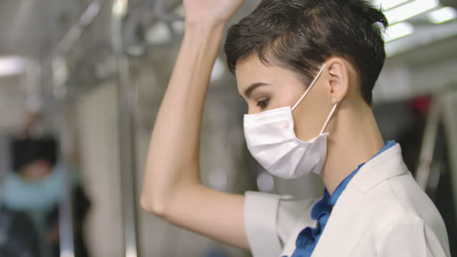 Portrait female passenger on BTS or metro subway train wear mask protection pollution and pandemic of virus, keep social distancing to prevent covid-19 while commuting on working. Behavior in public places during disease outbreaks. New normal lifestyle.
