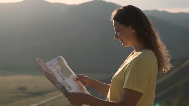 Portrait. Female tourist stands on the edge of a cliff with a map in her hands and looks for a route for travel Portrait. Beautiful female tourist in shorts and a T-shirt stands on the edge of a cliff with a map in his hands and is looking for a route for travel california map stock videos & royalty-free footage