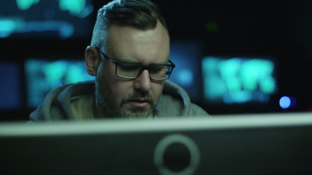 Portrait footage of concentrated male employee working on a computer in a dark office room with display screens with maps and data. video