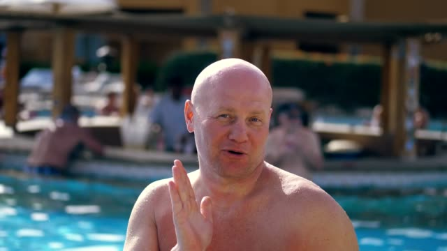 vídeos de stock e filmes b-roll de portrait, funny bald middle-aged man, with a naked torso, something fun sings, dances, by the pool on vacation, in summer - água parada