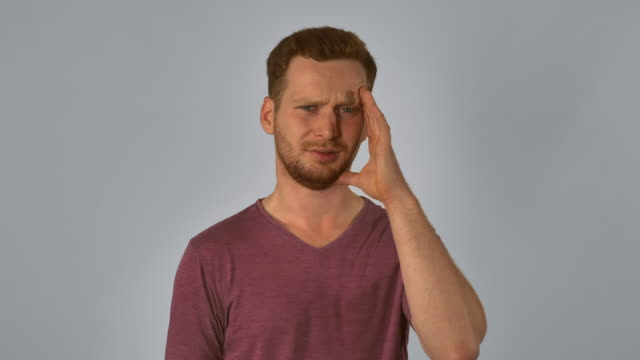 portrait ginger has migraines caucasian guy with red hair suffers from a headache. handsome redhead men wearing in casual t-shirt. young caucasian man on grey background dyed red hair stock videos & royalty-free footage