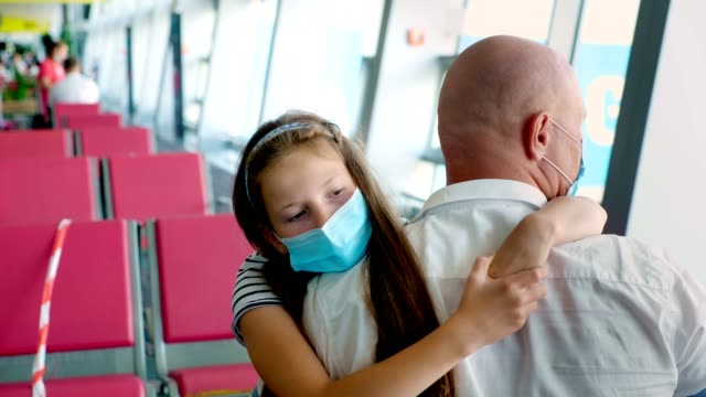 portrait, girl child in protective mask hugs her father, at airport, against background of empty seats in the departure lounge. flights opened after coronavirus epidemic video