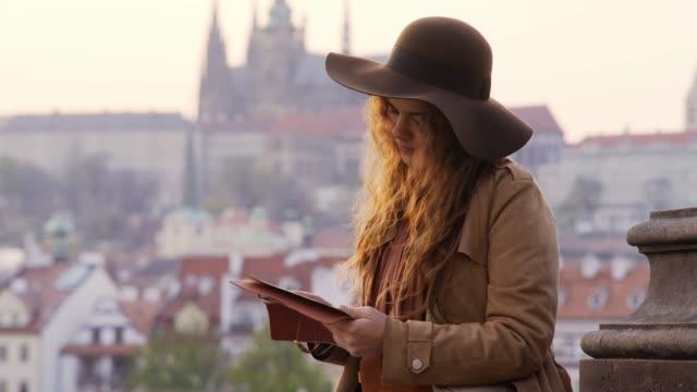 Portrait girl making notes on Charles bridge in Prague