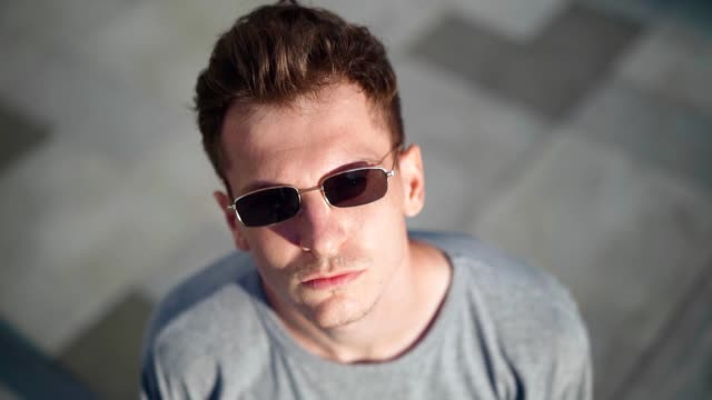 Portrait Handsome serious tough man dresses his black sunglasses and looks at the camera. Caucasian stylish young guy on the blurred background. Casual style of clothing. Slow motion.