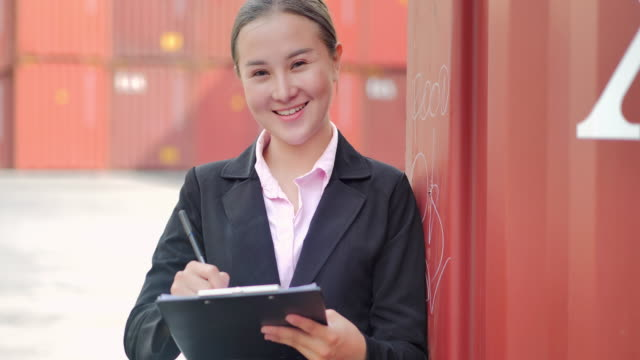 Portrait happy asian women engineer looking at camera and check loading containers box from cargo freight.Delivery,Commerce,Growth,Connection,Business,Empowerment,Leadership,Women in STEM,Industry and Transportation concept.Cargo Containers video