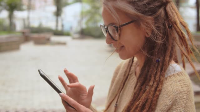 portrait happy girl use phone outdoors side view smiling young caucasian woman with dreadlocks and eyeglasses using app on smartphone swipe left and right locs hairstyle stock videos & royalty-free footage