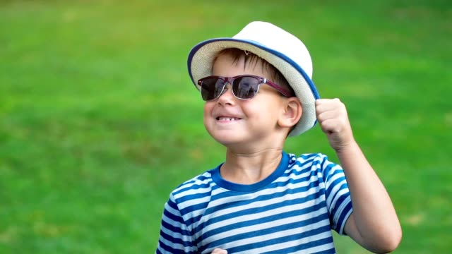 Portrait happy smiling little boy in sunglasses and hat having fun dancing in summer park
