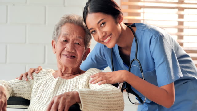Portrait happy volunteer young black woman nurse caretaker with asian senior grandmother patient looking at camera stay at home to prevent epidemics of Coronavirus or Covid-19.Healthcare and medicine,Caretaking,Retirement,Family,Charity,Nursing home. video