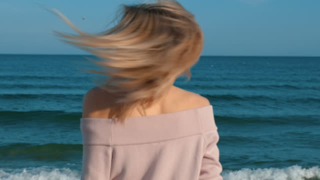 portrait happy young blonde woman in yellow sunglasses dancing rhythmically moving his hands spinning whirls seashore and dances, flirts, looks at camera, enjoys sun's rays, smiles against blue sea - кофеин стоковые видео и кадры b-roll