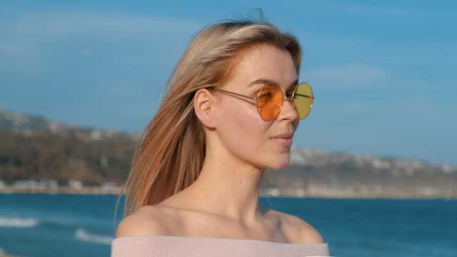 portrait happy young blonde woman with yellow glasses with hand straightens hair developing in wind on seashore, paper cup with coffee, smiles against blue sky, blue sea slow motion summer. lifestyle - кофеин стоковые видео и кадры b-roll