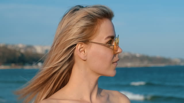 portrait happy young blonde woman yellow sunglasses stands on seashore turning his head slowly and enjoys sun's rays, smiles against blue sky and blue sea in summer slow motion. lifestyle. relax - кофеин стоковые видео и кадры b-roll