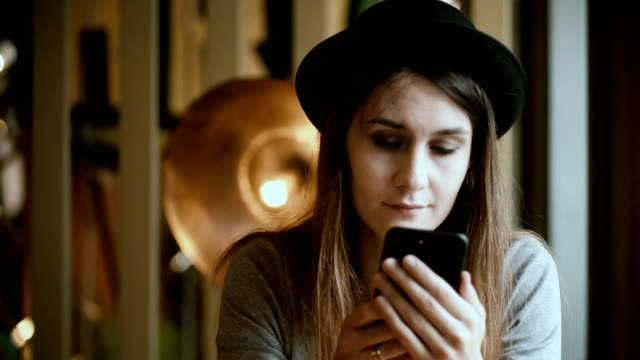Portrait if beautiful woman sitting in cafe and using the smartphone. Attractive female in hat chatting from cellphone video
