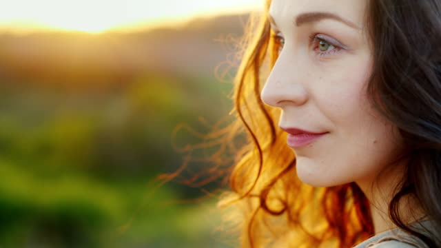 Portrait in profile of a young woman. Smiling, looking at the camera. Evening before sunset. Slow Motion video Portrait of an attractive middle-aged woman. He looks and smiles at the camera. Behind the setting sun beautifully highlights her hair. HD video free stock without watermark stock videos & royalty-free footage